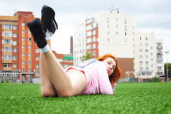 Beautiful sporty red-haired girl resting on grass after sport Royalty Free Stock Photo