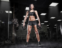 Beautiful sporty sexy woman doing squat workout in gym. Nice sexy woman doing workout with big dumbbell Royalty Free Stock Photography