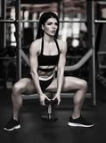 Beautiful sporty sexy woman doing squat workout in gym stock images