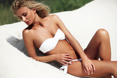 Beautiful, sporty and sexy woman lying on the beach Royalty Free Stock Photos