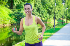 Beautiful sporty slim woman running in park. Beautiful sporty slim woman running in summer park Stock Images