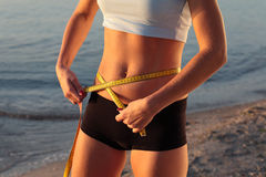 Beautiful sporty woman body with yellow measure Stock Images