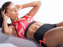 Beautiful sporty woman doing exercise for abs on white backgroun Royalty Free Stock Photography
