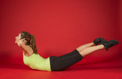 Beautiful sporty woman doing exercise. Woman exercising workout fitness aerobic exercise posture on studio over red background Royalty Free Stock Photos
