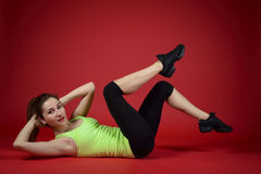 Beautiful sporty woman doing exercise on the floor. Woman exercising workout fitness aerobic exercise posture on studio Stock Photos