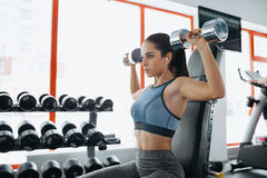 Beautiful sporty woman doing power fitness exercise at sport gym. Concentrated girl with ponytail in blue top sitting on the bench and working out with stock image