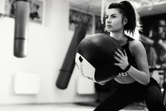 Close up photo of beautiful sporty young woman doing squats with med ball. Fitness and healthy lifestyle concept royalty free stock photography