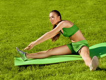 A beautiful sporty woman doing stretching exercise against natur Stock Image