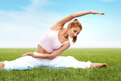 A beautiful sporty woman doing stretching exercise against natur Stock Photography