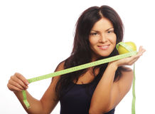 Beautiful sporty woman with green apple and measuring tape Stock Photo