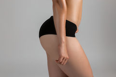 Beautiful sporty woman hips.  on graybackground. Beautiful sporty woman body Stock Images