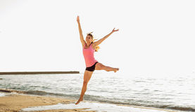Beautiful sporty woman jumping on seaside, gymnast female doing royalty free stock images