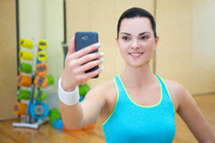 Beautiful sporty woman making selfie photo on smartphone in gym royalty free stock photos
