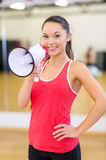 Beautiful sporty woman with megaphone at gym Royalty Free Stock Images