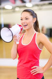 Beautiful sporty woman with megaphone at gym Royalty Free Stock Photos
