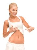 Beautiful sporty woman pointing at her abs Royalty Free Stock Images