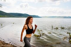 A beautiful sporty woman runing on the shore of a lake in sports. Wear. Girl is exercising Stock Photos