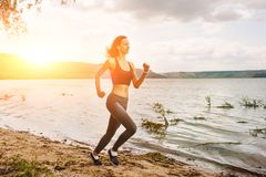 A beautiful sporty woman runing on the shore of a lake in sports. Wear. Girl is exercising Stock Image