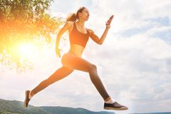 A beautiful sporty woman runing on the shore of a lake in sports. Wear. Girl is exercising Royalty Free Stock Photography