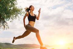 A beautiful sporty woman runing on the shore of a lake in sports. Wear. Girl is exercising Royalty Free Stock Photos