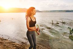 A beautiful sporty woman runing on the shore of a lake in sports. Wear. Girl is exercising Stock Photo