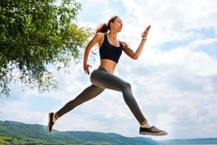 A beautiful sporty woman runing on the shore of a lake in sports. Wear. Girl is exercising Royalty Free Stock Photo