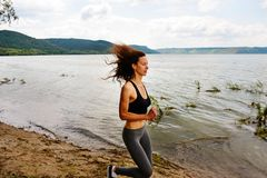 A beautiful sporty woman runing on the shore of a lake in sports. Wear. Girl is exercising Royalty Free Stock Images