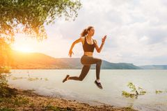 A beautiful sporty woman runing on the shore of a lake in sports. Wear. Girl is exercising Stock Photography