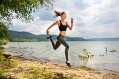 A beautiful sporty woman runing on the shore of a lake in sports. Wear. Girl is exercising Stock Images