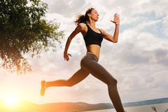 A beautiful sporty woman runing on the shore of a lake in sports. Wear. Girl is exercising Royalty Free Stock Image