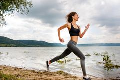 A beautiful sporty woman runing on the shore of a lake in sports stock photography