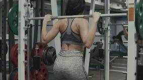 Beautiful sporty woman in sportswear doing squat workout in gym in slow motion stock video footage