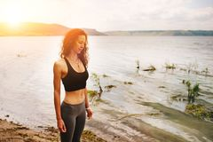 A beautiful sporty woman standing on the shore of a lake in spor. Tswear and preparing for an exercising Royalty Free Stock Photography