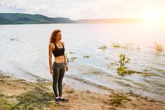 A beautiful sporty woman standing on the shore of a lake in spor. Tswear and preparing for an exercising Stock Images