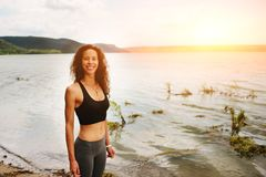 A beautiful sporty woman standing on the shore of a lake in spor. Tswear and preparing for an exercising Royalty Free Stock Photos