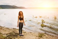 A beautiful sporty woman standing on the shore of a lake in spor. Tswear and preparing for an exercising Stock Image