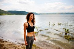 A beautiful sporty woman standing on the shore of a lake in spor. Tswear and preparing for an exercising Stock Photos