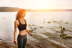 A beautiful sporty woman standing on the shore of a lake in spor. Tswear and preparing for an exercising Royalty Free Stock Photo