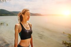 A beautiful sporty woman standing on the shore of a lake in spor. Tswear and preparing for an exercising Stock Photo
