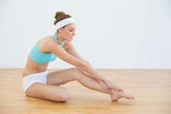 Beautiful sporty woman stretching her leg sitting on the floor. In sports hall stock image