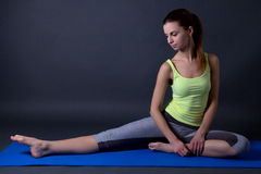 Beautiful sporty woman stretching leg on the floor over grey Stock Photography