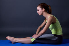 Beautiful sporty woman stretching legs on yoga mat over grey Royalty Free Stock Photography