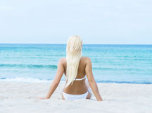 Beautiful and sporty woman in a swimsuit relaxing on the beach Royalty Free Stock Photo
