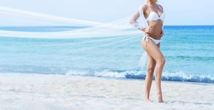 Beautiful and sporty woman in a swimsuit relaxing on the beach Royalty Free Stock Photography
