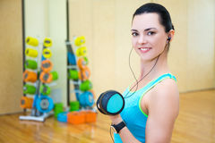 Beautiful sporty woman working out and listening music in gym Stock Photos