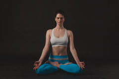 Beautiful sporty yogi girl practices yoga asana. Over black background Royalty Free Stock Image
