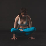 Beautiful sporty yogi girl practices yoga asana. Over black background Stock Image