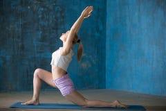 Beautiful sporty young lady doing Anjaneyasana Posture. Portrait of beautiful young woman dressed in shorts and white top enjoying yoga indoors. Yogi girl royalty free stock photo