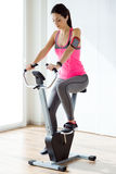Beautiful sporty young woman doing exercise in gym. Stock Photos