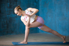Beautiful sporty young woman doing Revolved Side Angle Pose Stock Image